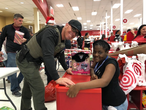 Police officer smiling with participating kid during Shop With A Cop event at Target