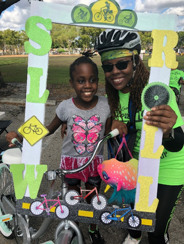 Chief Constance Y. Stanley and participating kid smiling together with a Slow Roll frame at the event