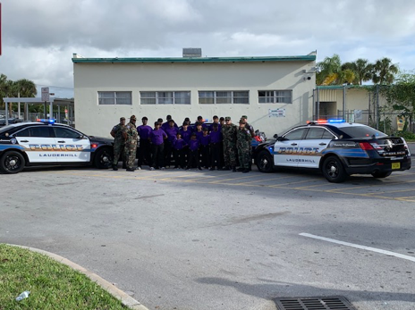 Group picture of Officers and Participating Kids by Lauderhill police cars