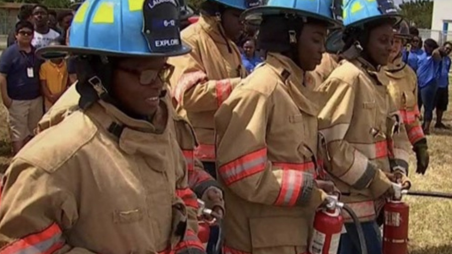 Lauderhill 6-12 Students training in fire uniforms with fire extinguishers