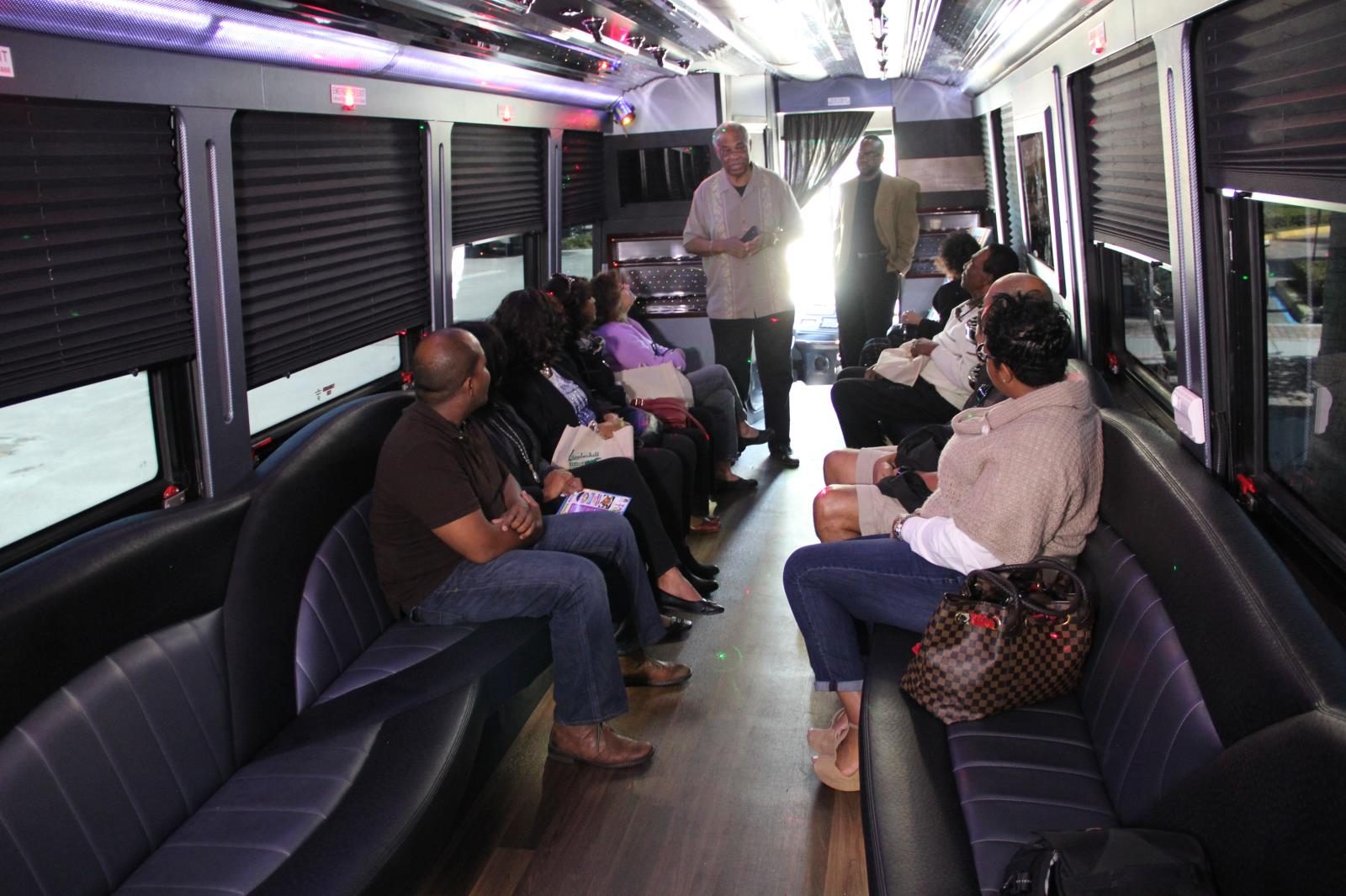 Comm. Benson speaks to tour participants on bus