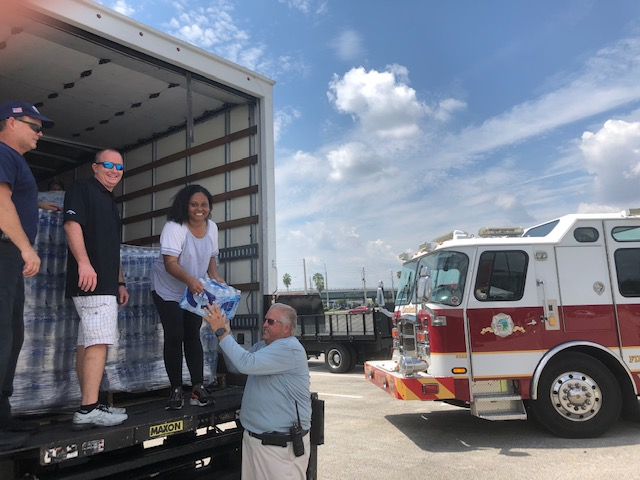 Commissioner Denise D. Grant working with Firefighters to load the trucks and receiving water from Fire Chief Celetti