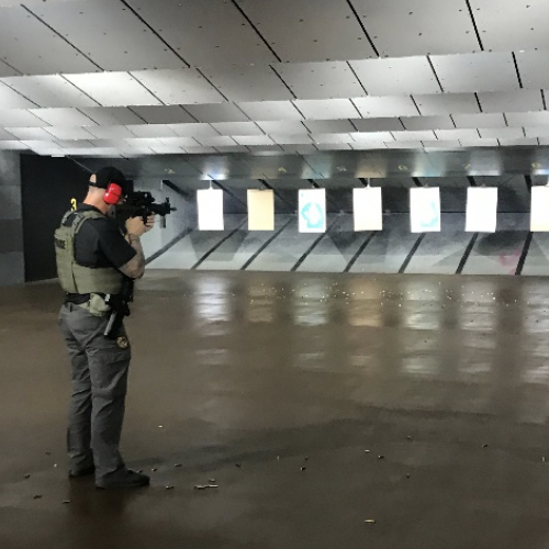 officer standing for rifle target practice