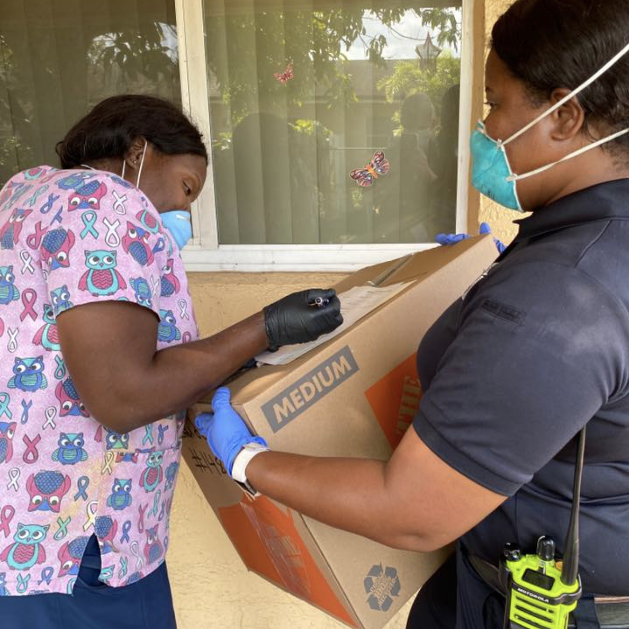 Fire Inspector Sheniqua Johnson delivers boxed supplies to nurse
