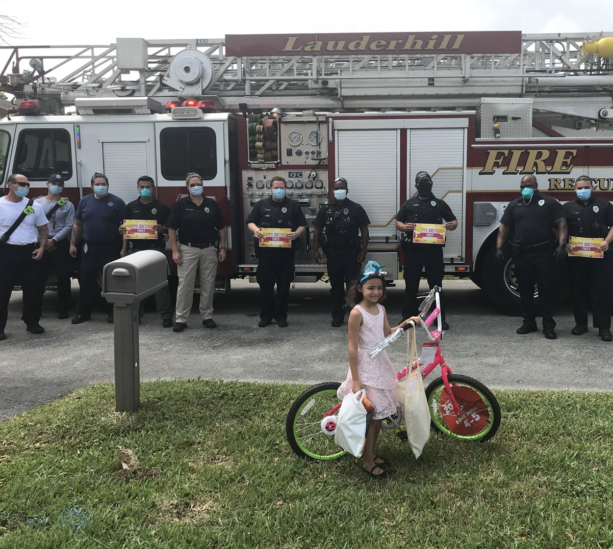 Emily Becker stands in front of fire engine and staff on lawn with her gifts