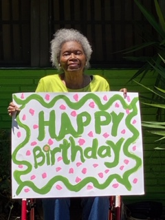 Mrs. Lillie Fye holding a painted sign that says Happy Birthday