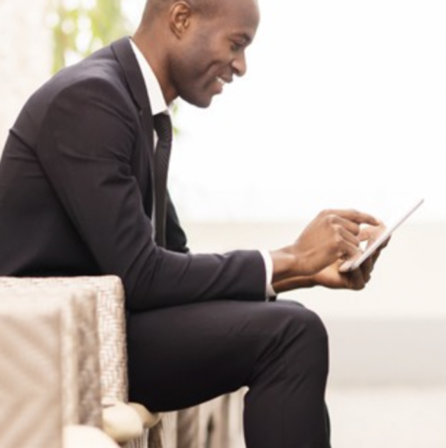 Man in black business suit using a tablet device
