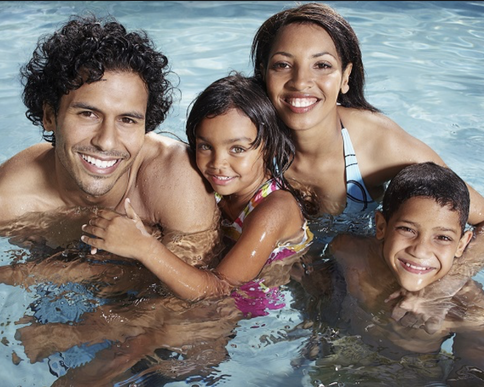 Two adults and two children standing in a swimming pool.
